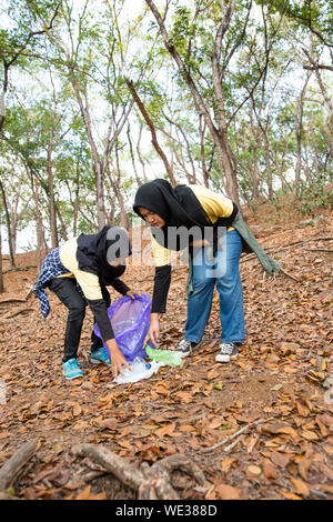 Two young woman hijab volunteers cleaning rubbish from park together - Stock Photo