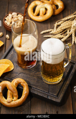 Various types of freshly poured beer - light and dark and snack variety. Dark wooden background. - Stock Photo
