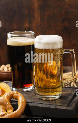 Various types of freshly poured beer - light and dark and snack variety. Dark wooden background. Copy space. - Stock Photo