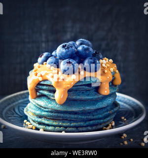 Blue spirulina pancakes topped with peanut butter, blueberries and popped quinoa - Stock Photo