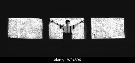 Rear View Of Boy Standing With Arms Outstretched Against Dirty Windows - Stock Photo