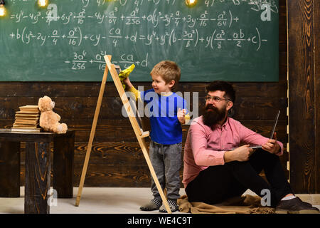 Smiling teacher in glasses sitting on the floor while kid is having fun. Little schoolboy wiping chalkboard. - Stock Photo