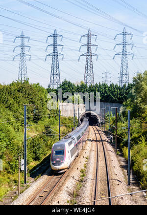 A double-decker TGV Duplex high-speed train in Carmillon livery is entering a tunnel under a row of transmission towers on the LGV Atlantique railway. - Stock Photo