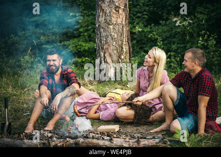 Two couples camping in woods. Guys in red lumberjack shirts cooking sausages over fire. Smiling friends relaxing around campfire in the evening - Stock Photo