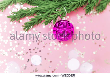 Pink toy on the branches of a Christmas tree on the pink background with glitters and bokeh flat lay. Christmas post card. - Stock Photo