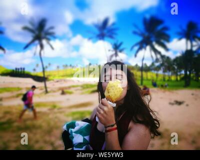 Young Woman Eating Pineapple While Standing On Field - Stock Photo
