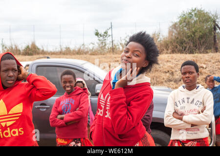 Mbabane, Swaziland - August 31, 2017: Group of happy smiling african beautiful young girls in bright red clothes outdoors close up - Stock Photo