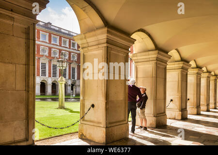 9 June 2016: Hampton Court, Richmond, London, UK - The Colonnade in Fountain Court, two male tourists sightseeing. The Palace was begun building in 15 - Stock Photo