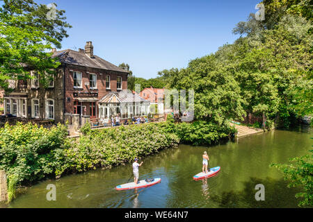 29 June 2019: Norwich, Norfolk, UK - Couple paddle boarding on the River Wensum, with the Red Lion Hotel in the background. Bright summer day, lots of - Stock Photo