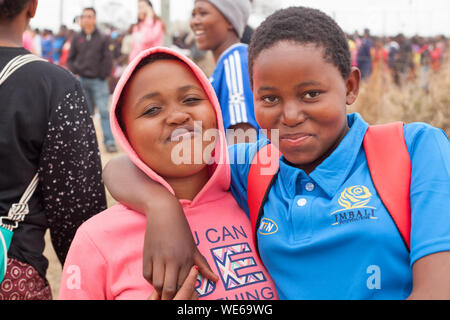 Mbabane, Swaziland - August 31, 2017: two happy smiling african beautiful young girls embrace outdoors on people celebrating Umhlanga rite background - Stock Photo
