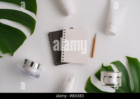 Directly Above Shot Of Spiral Notebook With Leaves And Beauty Products On Table - Stock Photo
