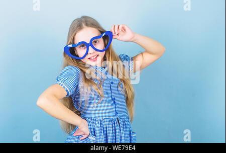 Fashion eyewear. Kid girl heart shaped eyeglasses. Girl adorable smiling face fall in love. Child charming smile blue background. Kid happy lovely enjoy childhood. Heart symbol of love. Power of love. - Stock Photo