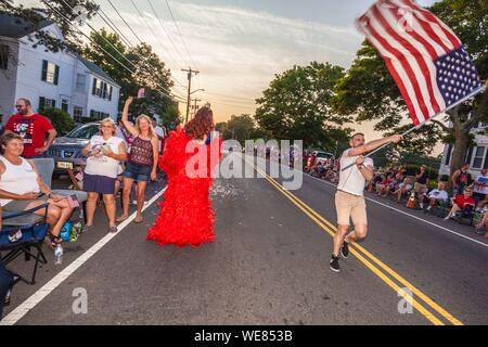 United States, New England, Massachusetts, Cape Ann, Gloucester, Gloucester Horribles Traditional Parade, July 3, man marching with US flag - Stock Photo