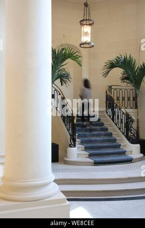 France, Paris, Hotel du Louvre, woman climbing the stairs in the colonnade lobby of the Hotel du Louvre belonging to the hyatt group - Stock Photo