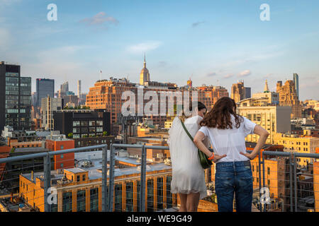Chelsea New York, rear view in summer of two women friends looking down at buildings in the Chelsea area of downtown Manhattan, New York City, USA - Stock Photo