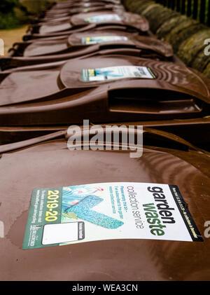 A line of brown garden waste wheelie bins outside a community garden. - Stock Photo