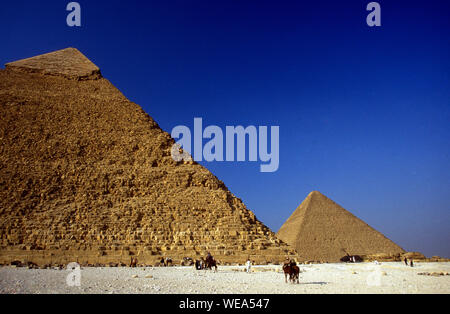 People On Desert Landscape Against Pyramids And Sky - Stock Photo