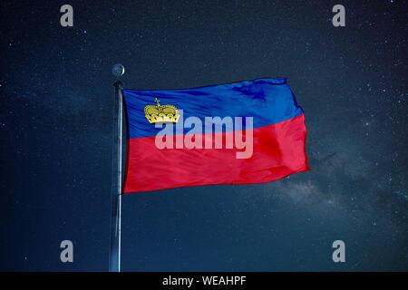 Flag Of Liechtenstein Against Star Field Sky - Stock Photo