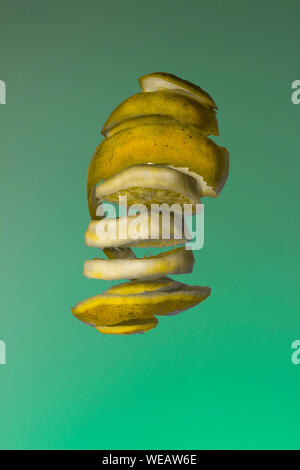Close-up Of Orange Slices Against Green Background - Stock Photo