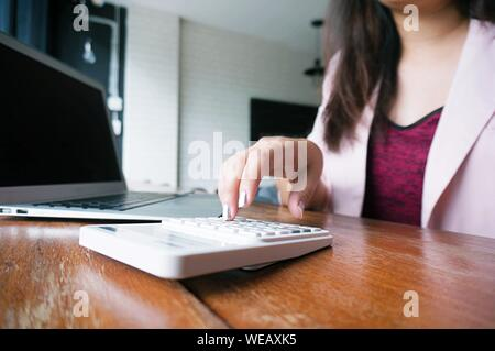 Midsection Of Businesswoman Using Calculator By Laptop While Working In Office - Stock Photo