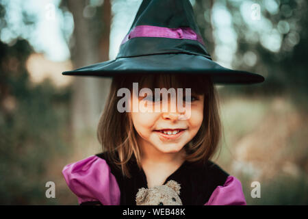 Smiling girl disguised as a witch in the woods during Halloween - Stock Photo