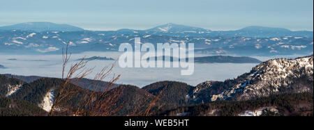 Moravskoslezske Beskydy mountain range with highest Lysa hora hill on the middle from Horna luka hill in winter Mala Fatra mountains in Slovakia - Stock Photo