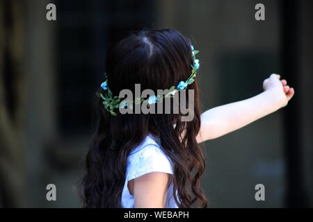 Rear View Of Girl Wearing Floral Wreath - Stock Photo