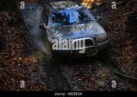 Offroad car going through deep mud. SUV covered with dirt goes through forest. Car with fall nature on background. 4x4 racing concept - Stock Photo
