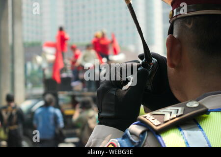 Close-up Of Police Man Using Walkie-talkie In City - Stock Photo