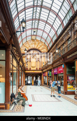 Female busker playing Chello in Central Arcade in Newcastle upon Tyne. England. UK - Stock Photo