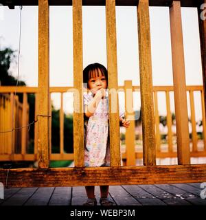Portrait Of Girl Standing On Boardwalk Seen Through Wooden Railing - Stock Photo