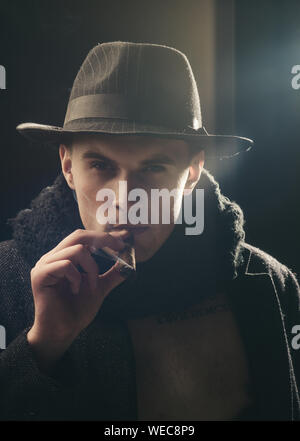 Vintage detective concept. Man in coat, hat smoking cigar, dark background. Macho on mysterious face, detective, investigator, agent. Guy in old fashi