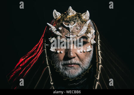 Sorcerer in metallic hood absorbed by darkness, magic and fantasy concept. Demon head with sharp thorns and warts on black background. Bearded man wit - Stock Photo