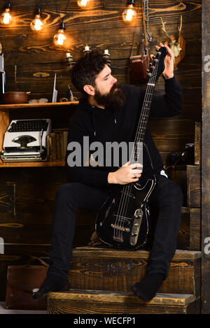 Favourite activity. Man bearded musician enjoy evening with bass guitar, wooden background. Man with beard holds black electric guitar. Guy in cozy wa - Stock Photo