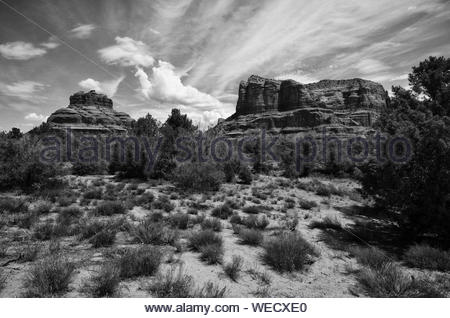Plants Growing By Rock Formations Against Cloudy Sky - Stock Photo