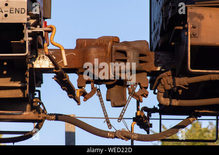 Close up of train joint between cars and break system lines on a train track in evening sunshine. - Stock Photo