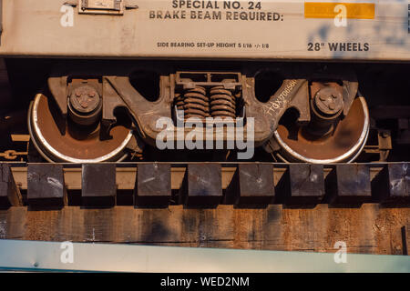 Close up of train wheels and break system in motion on track on wooden train bridge.' - Stock Photo