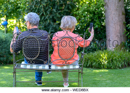 Rear view of senior couple sitting on bench in garden while using smartphones - Stock Photo