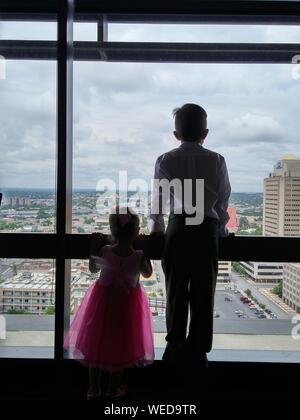 Rear View Of Siblings Looking City Through Window - Stock Photo