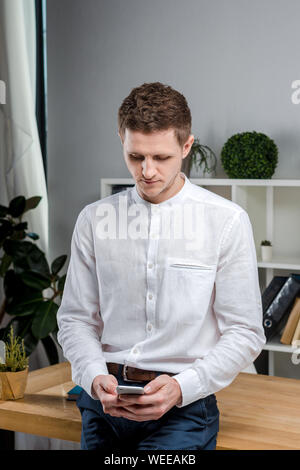 Attractive young businessman using a cell phone. Cheerful Businessman With Smartphone Standing In An Office. Portrait of man in office with telephone - Stock Photo