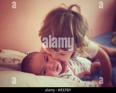 Close-up Of Girl Kissing Toddler Brother On Bed At Home - Stock Photo