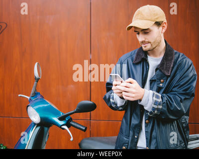 Young Man Standing By Scooter In City - Stock Photo