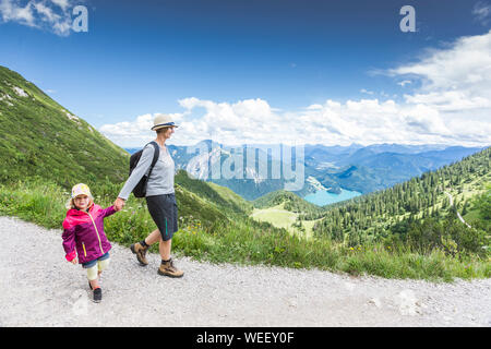 Mother And Daughter Walking On Mountain Against Sky - Stock Photo