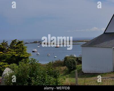l'île de molène et son merveilleux port et ses bateaux multicolors et ses quais en granit et un banc bleu et blanc et l'île prise depuis le large - Stock Photo