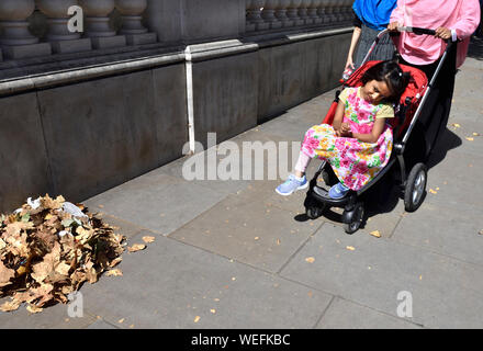 London, England, UK. Muslim faily - small girl in a pushchair - Stock Photo