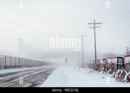 Power Lines On Snow Covered Road During Foggy Weather - Stock Photo