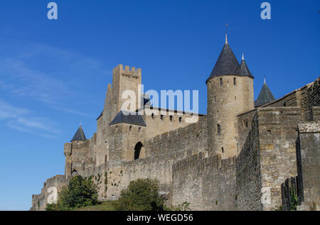 Carcassonne, ancient fortified city on the top of a hill in Languedoc-Roussillon on the Aude River, France, Europe. Outer rampart walls with blue sky - Stock Photo