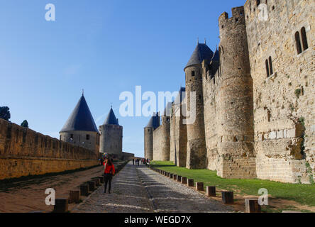 Tourists and balloon seller sightseeing between rampart walls of Carcassonne historic stone fortress on sunny day with blue sky. France, Europe - Stock Photo
