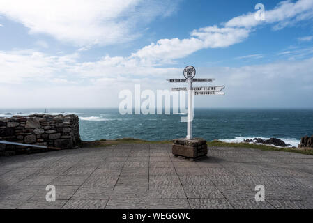 A signpost at Land's End on 20 August, 2016, with mileage and direction to New York, John O'Groats, China, Isles of Scilly, Longships Lighthouse. - Stock Photo