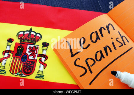 Learn Spanish written in the notebook with flag. - Stock Photo